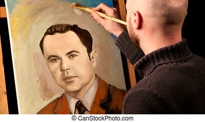 Talanted painter paints a picture, man, of oil paint brush with palette in his hand, on easel, black background