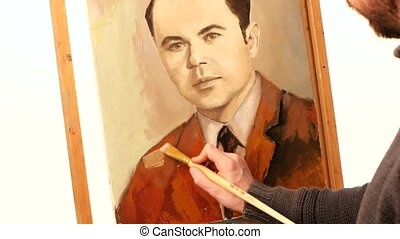 Talanted painter paints a picture of man by oil paint brush with palette in his hand, on easel, white background