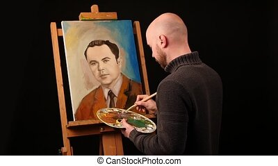 Talanted painter paints a picture of man by oil paint brush with palette in his hand, on easel, black background, slow motion