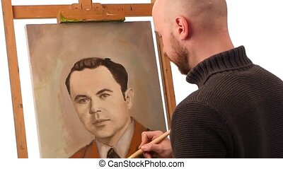 Talanted painter paints a picture of man by oil paint brush with palette in his hand, on easel, white background, slow motion