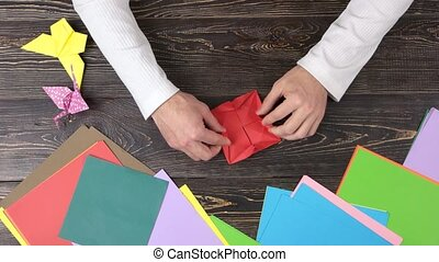 Talent and creativity. Close up male hands folding origami...