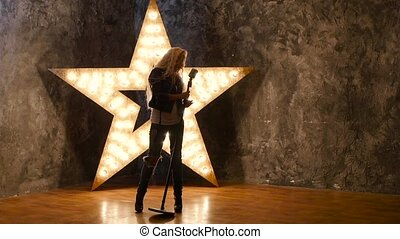talent girl singer with curly hair, microphone, dances. shining star in the background. slow motion, silhouette