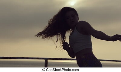 Talented and full of the positive teenager girl dancing on the pier by the sea at sunset