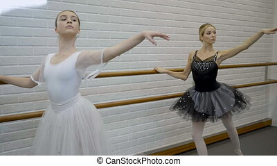 Talented ballerinas are moving near barre in ballet school....