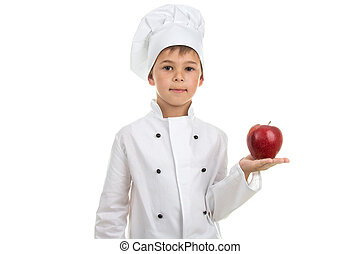 Talented cute boy in white chef uniform holding red apple on white background