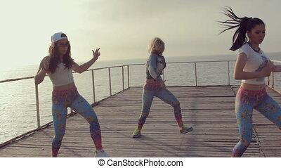 Talented energetic girl dancing twerk in sunset by the sea