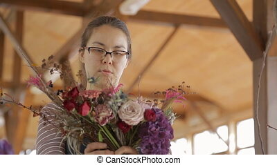 Talented florist creates floral bouquet standing indoors....