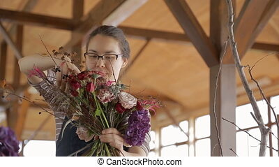 Talented florist creates floral bouquet, standing indoors....