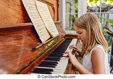Talented little girl playing piano in modern living room