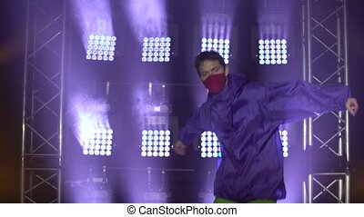 Talented male dancer is performing hip-hop dance indoors in modern studio concentrated on moves and technique. People and occupation concept. Dark studio with smoke and neon lighting. Dynamic lighting effects. Close up.