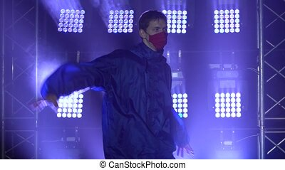 Talented male dancer is performing hip-hop dance indoors in modern studio concentrated on moves and technique. People and occupation concept. Dark studio with smoke and neon lighting. Dynamic lighting effects. Close up. Slow motion.