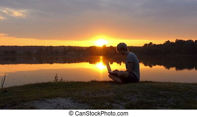 Talented Man Types on His Laptop on a River Bank at a Splendid Sunset