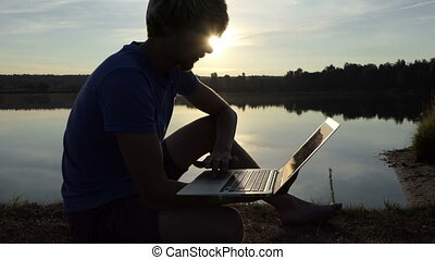 Talented man works with his laptop on a lake bank in slo-mo