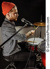 talented caucasian musician contemporaneously play on drums and sing on microphone. professional drummer preparing for rock concert, practice in dark studio. music concept