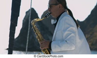 Talented saxophonist performs jazz on saxophone at yacht
