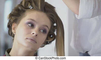 Talented stylist does hairstyle for seated woman in beauty salon. She separates thin strands of light hair and combs carefully, while makeup artist applies powder to temple, with quick movement. Two experts work together, which significantly speeds up creation of image for beautiful client.