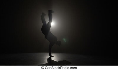 Talented young boy silhouette performing break dancing tricks in front of the spotlight in slow motion