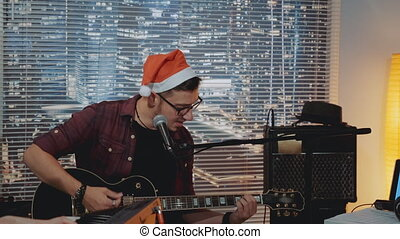 Talented young man in Santa hat recording his new track in home studio