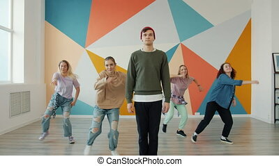 Talented young people guy and girls are performing modern dance in studio practicing indoors smiling wearing trendy clothing. Youth culture and activities concept.