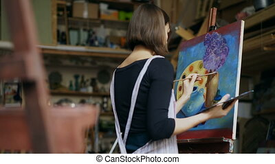 Talented young woman artist painting picture on canvas in...