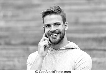 Talk concept. Happy man talk on mobile phone. Young guy use smartphone to talk outdoor. Carefree talk with friend. Sharing good news