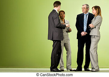 Portrait of several smart associates talking to each other after meeting or conference