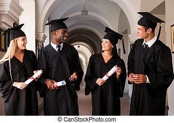 Talking about bright future. Four college graduates in graduation gowns walking along university corridor and talking
