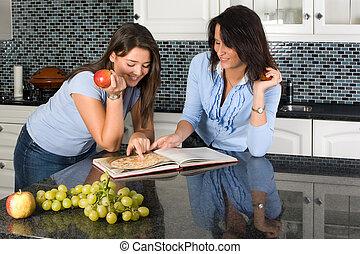 Two friends discussing recipes over a cookbook