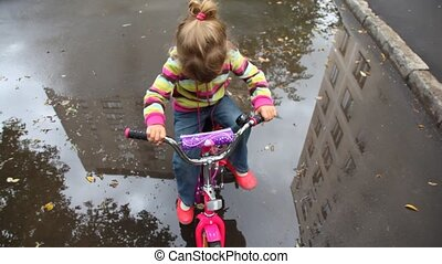 talking little girl sits on bicycle on wet asphalt with puddles