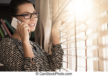 Talking on the phone next to the window