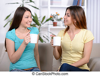Talking - Two happy young female friends with coffee cups...
