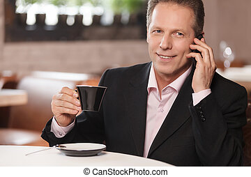 Talking to business partner. Cheerful businessman drinking coffee and talking at phone while sitting at restaurant