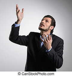 Talking to God. Bearded businessman in formalwear standing with his hands raised up while isolated on grey