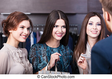 Talking to salesperson - Three girlfriends talk with...