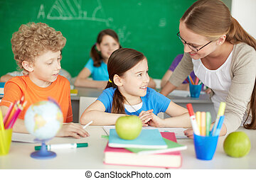 Talking to teacher - Portrait of diligent schoolkids and...