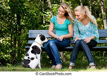 Talking to the dog - Two blond girls and a american bulldog...