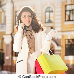 Talking with friend. Beautiful young women talking at the mobile phone and holding the shopping bags