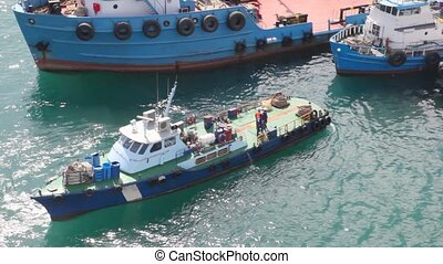 Talking workers on cutter near barges in port Fujairah in...
