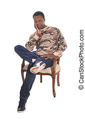 Tall African American man sitting in armchair