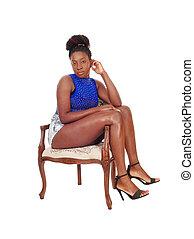 Tall African American woman sitting sideward in a chair