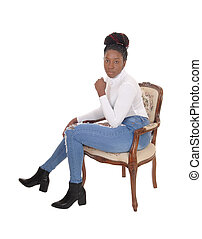 Tall African American woman sitting sideward in an old armchair