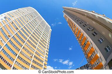 Tall apartment buildings under construction against a blue sky b