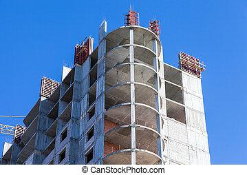 Tall building under construction against a blue sky