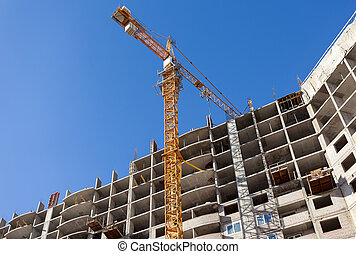 Tall buildings under construction with crane against a blue sky