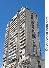 Tall concrete apartment building over blue sky