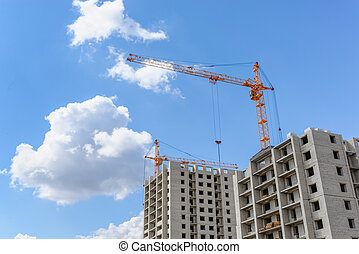 Tall cranes on a blue sky background