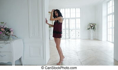 tall girl in red silk lingerie stands in a big white room