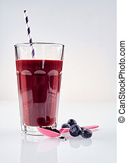 Single large glass of fresh blueberry and exotic acai berry blended beverage with one straw next to a pink spoon against a white background