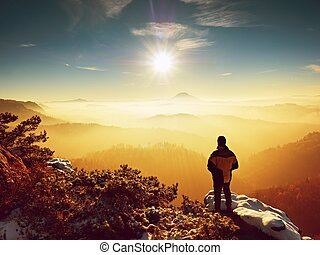 Tall hiker in black on rocky peak watch the world . Heavy...