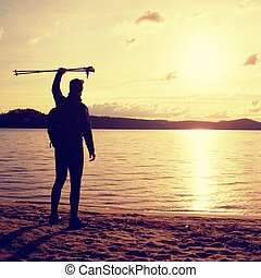 Tall hiker in dark sportswear with poles and sporty backpack on beach enjoy sunset at horizon. Magic autumn day.